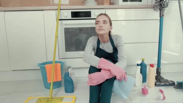 Zufriedene müde junge schöne Frau sitzt auf dem Boden in der Küche.