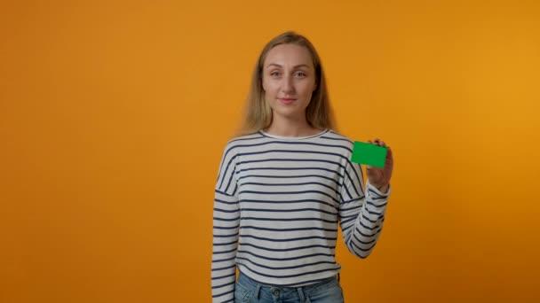 Mladá žena drží v ruce prázdnou kartu a ukazuje gesto prstem dolů..