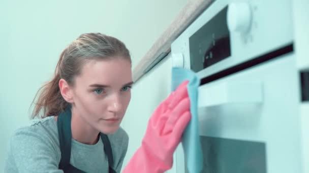Schöne junge Mädchen professionelle Reinigungskraft, wischt mit einem Lappen über den Ofen.
