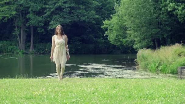 Egy hosszú szőke hajú fiatal nő gyönyörűen táncol. A kamerába néz..