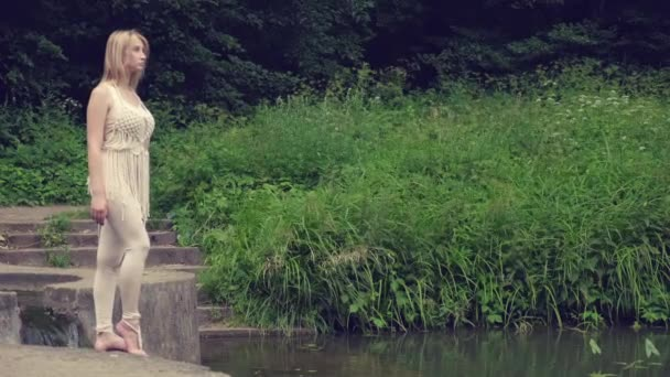 Egy karcsú lány áll a tó partján, és a távolba néz..