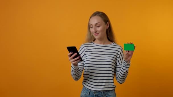 Žena dělá on-line nákupy z telefonu, drží slevovou kartu v ruce.