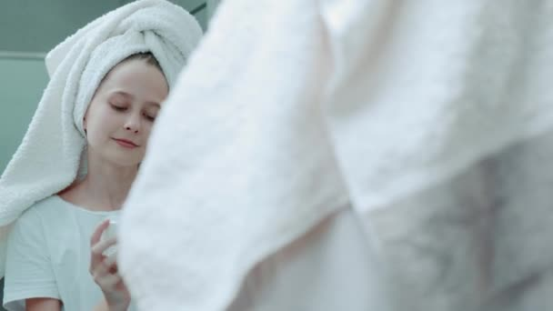 Krásná dívka s ručníkem na hlavě aplikuje hydratační krém na její obličej.