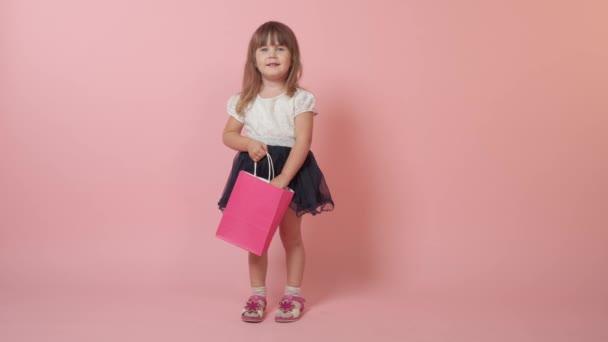 Krásná roztomilá dívka s nákupy v rukou. Krásné světlé slavnostní oblečení