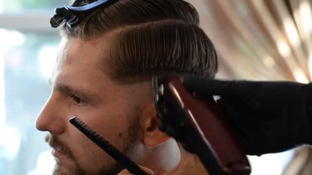 a hairdresser cuts a bearded young guy with a hair trimmer, combing the hair on his head. Work of the master in mens haircut in a barbershop