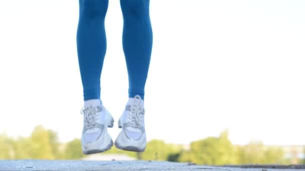 mladá rusovlasá dívka sportovec skákání lano na ulici. Aktivní životní styl. Sportovní ženské tělo v kamaších a tyrkysovém svršku, bílé tenisky, skákající ve vzduchu.