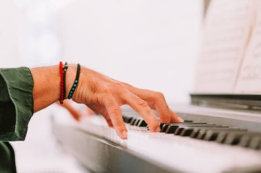 Male hands playing piano at home studio