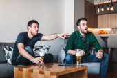 Two guys drinking beer watching sports on TV