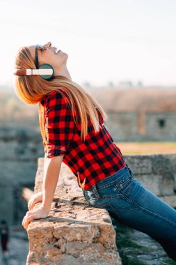 Young woman listening to the music on headphones outdoors