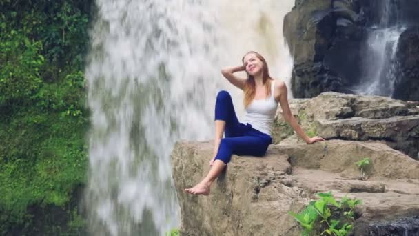 Woman sitting on a cliff next to Tegenungan Waterfall