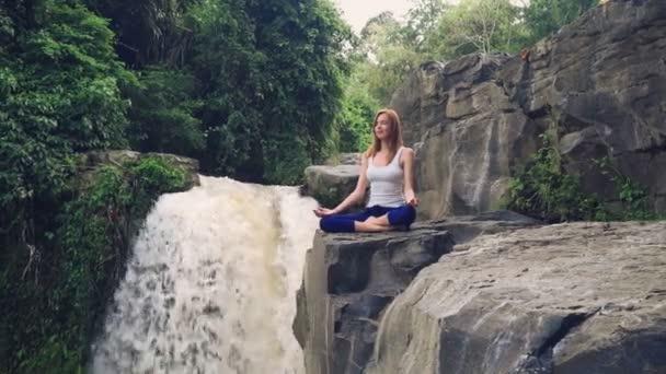 A jóga lótuszban ülő nő pózol a Tegenungan vízesés szélén.