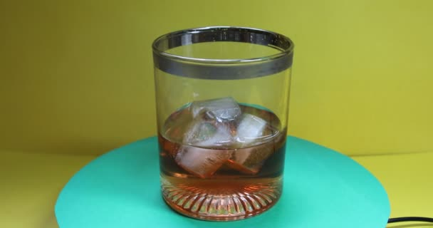 Az üveg frissítő whiskyvel és jégkockával forog.