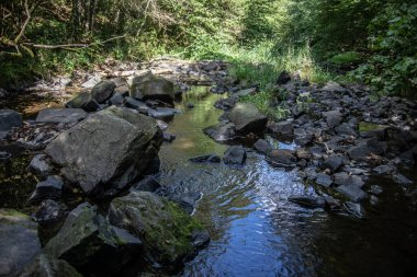 River course littered with rocks with waterfall in Siegerland
