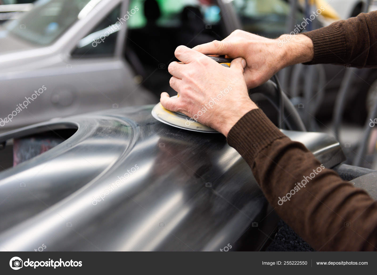 Car mechanic with dust mask grinds a car part in a service station