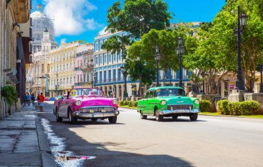 American pink 1957_Buick Super 56C convertible vintage car and a green 1955 Chevrolet 210 Bel air on the main street Paseo de Marti in Havana City Cuba - Serie Cuba Re