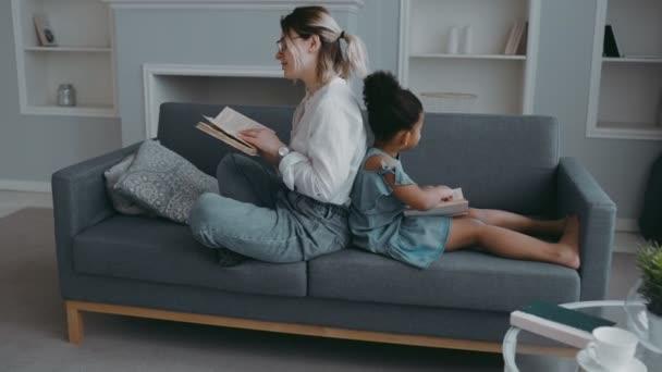 Mutter und afrikanische Tochter sitzen auf dem Sofa im modernen Wohnzimmer Rücken an Rücken und lesen Bücher. Mutterschaft und Kindheit. Konzept der Familienerholung multirassische Familie, Quarantäne, Isolation, häusliche Aktivitäten.