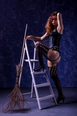 Sexy woman in a corset, stockings and with a broom posing on a dark background standing on a step ladder.