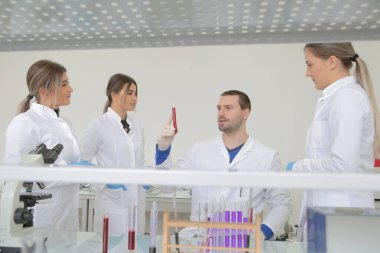 Group of young Laboratory scientists working at lab with test tu