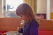 arckifejezések egy édes lány, miközben játszik otthon