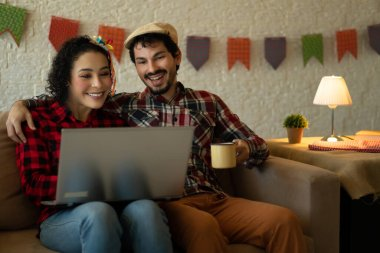 Happy cheerful Young adult brazilian couple relaxing and watching video during quarantine Inside the house in living room. Traditional brazilian june festival, party, celebration concept.