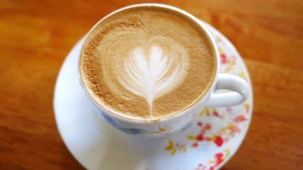 Šálek cappuccino káva na dřevěný stůl ráno.