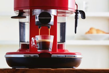 Making fresh coffee going out from a coffee espresso machine in glass transparent coffee cup