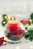 weihnachtliche Tischdekoration. Glasvase mit Stechpalme und roter Kerze.