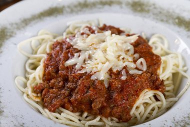 Delicious Spaghetti bolognese with grated parmesan cheese and thyme