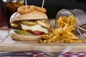 hausgemachter Hamburger mit Salat, Zwiebelringen, Pilzen, Tomatenscheiben, Essiggurken, Speck und Cheddar-Käse serviert mit gebratenen würzigen Pommes frites auf Holztischhintergrund.