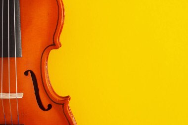 Classical music concert poster with orange color violin on yellow background with copy space for your text