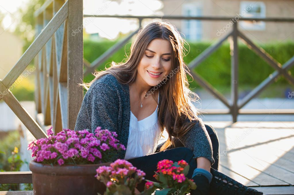 Beautiful young woman smiling, gardening in pots on the terrace,at home, with working gloves. Gardening as hobby and leisure concept.