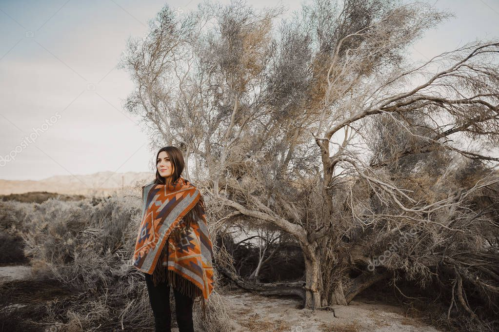 Smiling, beautiful hipster traveler girl in gypsy look in desert nature.  Artistic photo of young hipster traveler girl in gypsy look, in Coachella Valley in a desert valley in Southern California.