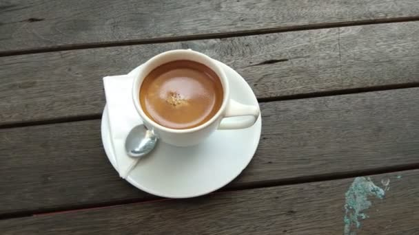 A cup of coffee on wooden background.