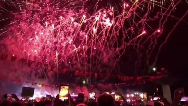 Lidé sledují ohňostroj show v noci a oni jsou nahrávání s jejich smartphone.