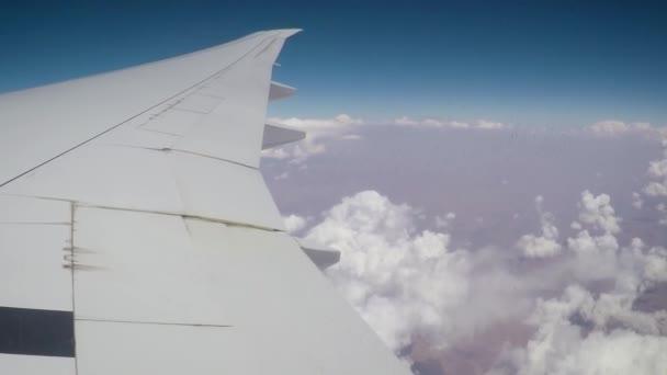 Wolken und Flügel aus dem Flugzeugfenster.