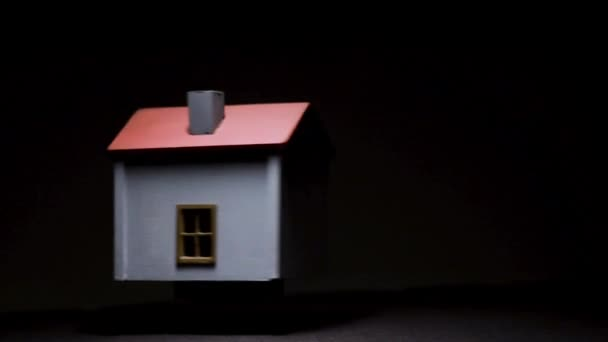 Otáčející se model domu na černém pozadí a s vysokým kontrastem.