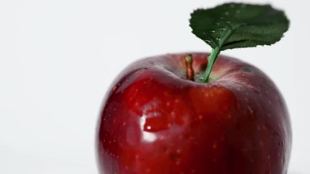 Self rotating red apple with a leaf on a white background.