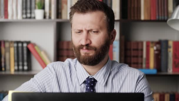 Bolest v lokti. Detailní záběr vousatého muže na počítačovém pracovišti a zažívajícího bolest a nepohodlí v lokti. Artritida, ortróza, koncepce bursitidy