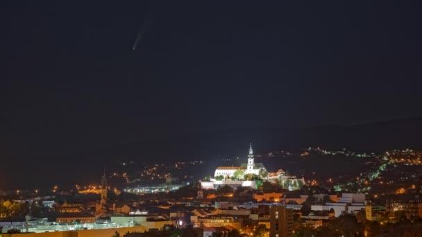 Kometa Neowise na noční obloze nad osvětleným městem a horami v pozadí