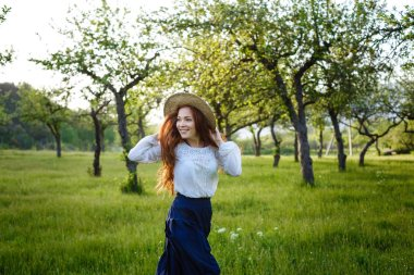 Summer portrait, beautiful freckled young woman wearing straw hat. Girl in the spring apple garden
