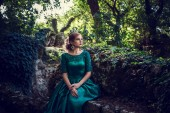 Fotografie Young woman wearing a green dress explores a magical forest