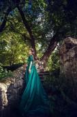 Mladá žena nosí zelené šaty zkoumá kouzelný les
