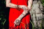 Fotografia Mehendi sulle mani di ragazze, mani della donna con il tatuaggio di mehndi marrone. Mani della ragazza sposa indiana con tatuaggi allhennè marrone