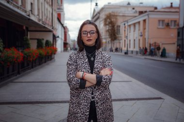 Beautiful young brunette woman walks in Moscow. In a trendy leopard jacket. Smiling and walking on the city. Going shopping.