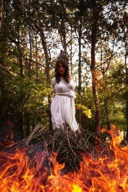 Sonbahar ormanında uzun beyaz elbiseli, gizemli gotik kadın. Karanlık fantezi yaratığı, bir cadı için şenlik ateşi