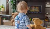Aranyos kisfiú és a plüssmackója TV-t néznek otthon a kanapén ülve a nappaliban.