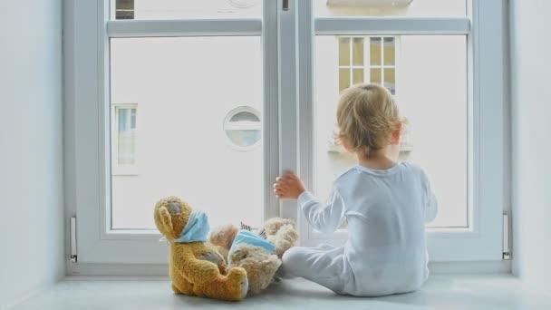 Dítě doma v karanténě, které si hraje u okna se svými nemocnými medvídky v lékařské masce proti virům během epidemie koronaviru a chřipky. Děti a nemoci Koncepce onemocnění COVID 2019