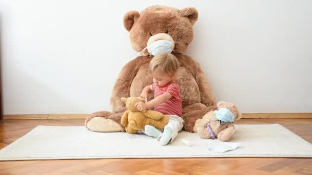Aranyos kisgyerek játszik a beteg plüssmacijaival, akik orvosi maszkot viselnek a vírusok ellen. Szerepjáték, doktorosdit játszani plüss játékkal. Gyermekek és influenza, koronavírus betegség fogalma.