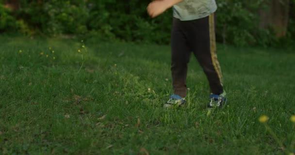 Porträt eines glücklichen kleinen Jungen, der im Sommer tanzt.