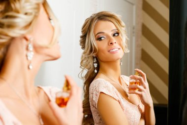 The girl in a stylish pink dress is strangled with perfume in front of the mirror